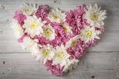 Le coeur fait de fleurs sur le blanc a rayé la vue supérieure de fond Images stock