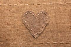 Le coeur fait de toile de jute se trouve sur un fond renvoyant Photographie stock