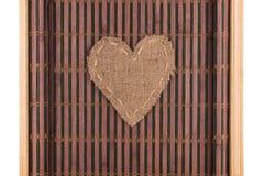 Le coeur fait de toile de jute se trouve sur un tapis en bambou avec les bords incurvés Photographie stock