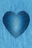Le coeur fait en tissu de denim se trouve sur le denim léger Photographie stock libre de droits