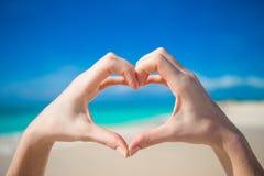 Le coeur a fait par le fond de mains l'océan de turquoise Image libre de droits