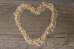 le coeur a garni de la farine d'avoine sur une table en bois Photographie stock libre de droits