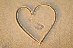 Le coeur handwrited sur le sable d'or avec la copie de pied dedans Photos stock