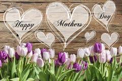 Le coeur heureux des textes de jour du ` s de mère avec le ressort en bois rustique de carte de voeux de fond de tulipes roses et Photographie stock libre de droits