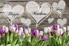 Le coeur heureux des textes de jour du ` s de mère avec le ressort en bois rustique de carte de voeux de fond de tulipes roses et Image stock