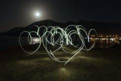 Le coeur léger de peinture forme au-dessus du fond de montagnes, de mer et de ville de nuit Amour Image libre de droits