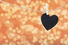 Le coeur noir a accroché sur la corde de chanvre d'isolement sur le fond blanc Images libres de droits