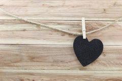 Le coeur noir a accroché sur la corde de chanvre d'isolement sur le fond en bois Photos stock