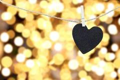 Le coeur noir a accroché sur la corde de chanvre sur le backgro coloré abstrait de bokeh Photographie stock libre de droits