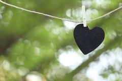 Le coeur noir a accroché sur la corde de chanvre sur le backgro coloré abstrait de bokeh Images libres de droits