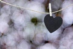 Le coeur noir a accroché sur la corde de chanvre sur le bokeh coloré abstrait Image libre de droits