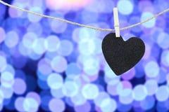 Le coeur noir a accroché sur la corde de chanvre sur le fond coloré abstrait de bokeh Photographie stock