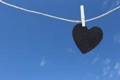 Le coeur noir a accroché sur la corde de chanvre sur le fond de ciel bleu Photo stock