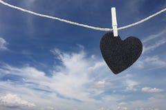 Le coeur noir a accroché sur la corde de chanvre sur le fond de ciel bleu Images libres de droits