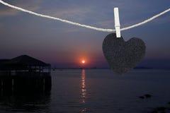 Le coeur noir a accroché sur la corde de chanvre sur le fond de coucher du soleil de vue Photos libres de droits