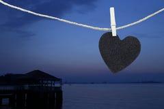 Le coeur noir a accroché sur la corde de chanvre sur le fond de coucher du soleil de vue Photo stock