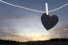 Le coeur noir a accroché sur la corde de chanvre sur le fond de lever de soleil Photographie stock