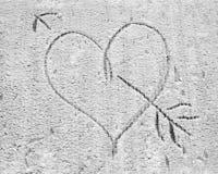 Le coeur percé avec une flèche, dessinée sur la neige Photographie stock libre de droits