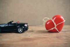 Le coeur qui a attaché avec la corde remorque en la voiture de sport Photographie stock