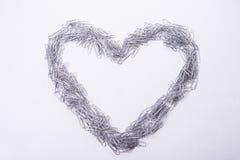 Le coeur rendent à partir des trombones prêt à textoter pour être écrivent sur le blanc Image stock