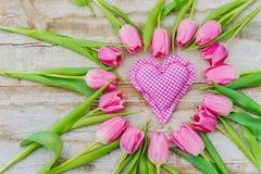Le coeur rose rustique encadré des tulipes roses fleurit sur le bois de vintage, fond romantique d'amour Photographie stock