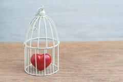 Le coeur rouge à l'intérieur de la cage à oiseaux miniature, aiment le romance ou l'ancrent Photographie stock libre de droits