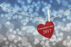 Le coeur rouge accroché sur la corde de chanvre et ont la Saint-Valentin heureuse des textes Photo libre de droits