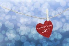 Le coeur rouge accroché sur la corde de chanvre et ont la Saint-Valentin heureuse des textes Photo stock