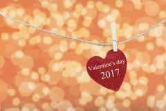 Le coeur rouge accroché sur la corde de chanvre et ont la Saint-Valentin heureuse des textes Images stock