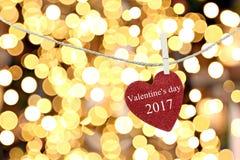 Le coeur rouge accroché sur la corde de chanvre et ont la Saint-Valentin heureuse des textes Photos libres de droits
