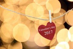 Le coeur rouge accroché sur la corde de chanvre et ont la Saint-Valentin heureuse des textes Image libre de droits