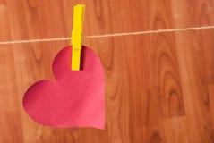Le coeur rouge a accroché sur la corde de chanvre sur le fond en bois Photographie stock libre de droits
