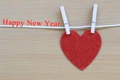 Le coeur rouge accrochant sur la corde et ont le texte de bonne année Photos libres de droits