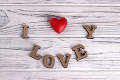 Le coeur rouge accrochant sur le blanc a peint le fond en bois rustique avec marquer avec des lettres je t'aime Image stock