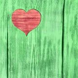 Le coeur rouge a découpé dans un conseil en bois vert Fond Photos libres de droits