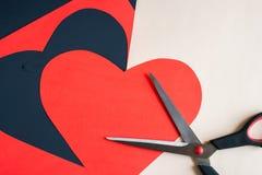 Le coeur rouge a découpé de la feuille de papier et les ciseaux sur l'obscurité ont peint b Photo libre de droits