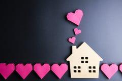 Le coeur rouge de jouet en bois de maison et de boîte de papier forment sur le backgrou noir Photographie stock libre de droits