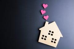 Le coeur rouge de jouet en bois de maison et de boîte de papier forment sur le backgrou noir Photo stock