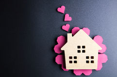 Le coeur rouge de jouet en bois de maison et de boîte de papier forment sur le backgrou noir Photographie stock