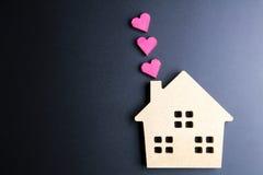 Le coeur rouge de jouet en bois de maison et de boîte de papier forment sur le backgrou noir Photos stock