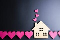 Le coeur rouge de jouet en bois de maison et de boîte de papier forment sur le backgrou noir Images stock