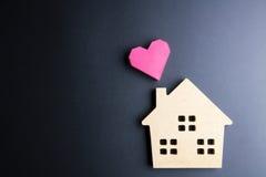 Le coeur rouge de jouet en bois de maison et de boîte de papier forment sur le backgrou noir Image stock