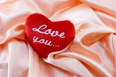 Le coeur rouge de peluche avec l'inscription : aimez-vous Photos libres de droits