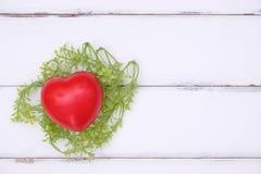 Le coeur rouge est dans le nid du ` s d'oiseau des feuilles Image stock