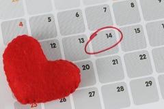 Le coeur rouge est placé sur le calendrier et le foyer dans le quatorzième jour Photo stock