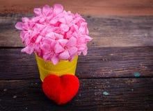 Le coeur rouge et la fleur rose avec de l'eau chutent sur la vieille table Photographie stock libre de droits