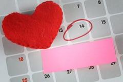 Le coeur rouge et la note de papier rose est placé sur le calendrier Photographie stock libre de droits