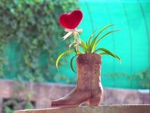 Le coeur rouge fait de serviette, bâton avec le crayon, ruban de lien et ananas de nain dans le vase a formé la botte Photographie stock