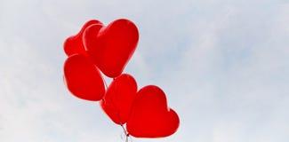 Le coeur rouge monte en ballon sur un fond de ciel Images stock