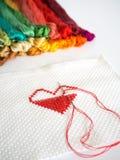 Le coeur rouge piquant forment sur le tissu blanc sur le fond blanc Images stock